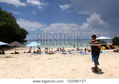 Bali, Indonesia - Feb 22, 2016: Tourist sunbathing and surfing at Pandawa beach , Bali Indonesia