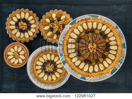 Five round traditional Polish Easter cakes with almonds raisins and walnuts on the dark fabric background.