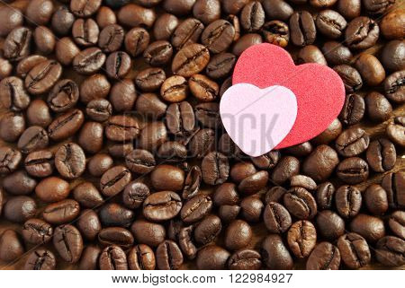 A simple grasp on the everyday coffee lover concept using gourmet coffee beans and a couple heart shape cutouts.