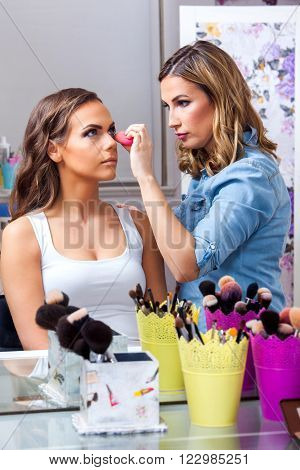Professional Make-up artist doing beautiful girl makeup in studio ** Note: Shallow depth of field