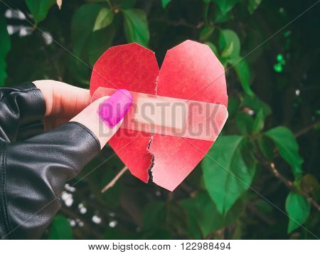 Broken handmade heart fixed with a Adhesive bandage.