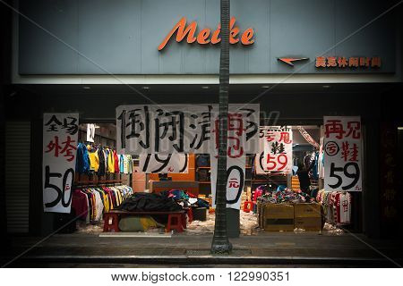 ZHONGSHAN GUANGDONG, CHINA-Mar 17, 2016:store hangs with 'shoes for 59'&'coat for 50'&'closing down sale'in Zhongshan Guangdong China.