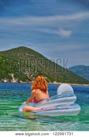 Young Woman in inflatable Matress relaxing in the Sea