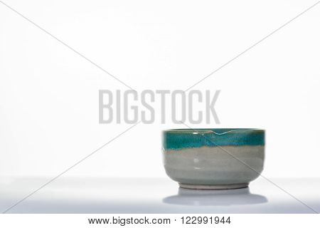 Asian ceramics cups on white with reflection