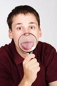Young Man Holding Magnifier And Showing Tongue Through It