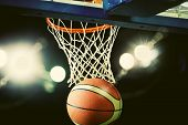 Basketball going through the hoop at a sports arena (intentional spotlight) poster