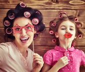 Funny family! Mother and her child daughter girl with a paper accessories. Beauty funny girl holding poster