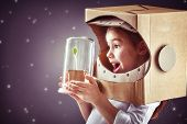 Child is dressed in an astronaut costume. Child sees a sprout in a glass case. The concept of enviro poster