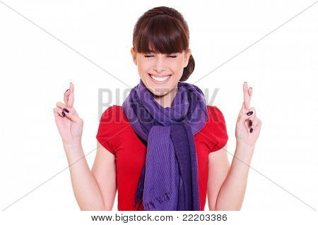 young smiley woman hoping hard with fingers crossed against white background