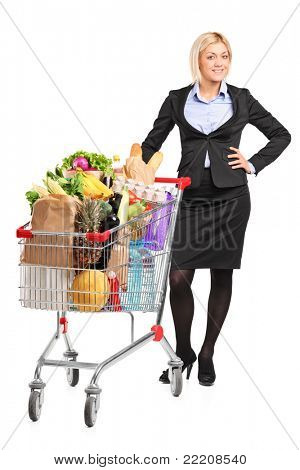 Full length portrait of a young woman posing next to a shopping cart full with groceries isolated on white background