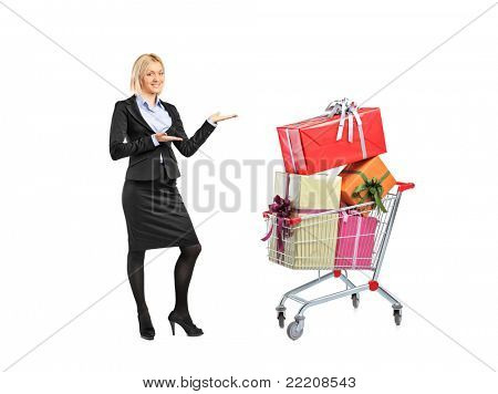 Full length portrait of a female in suit gesturing and a shopping cart isolated on white background