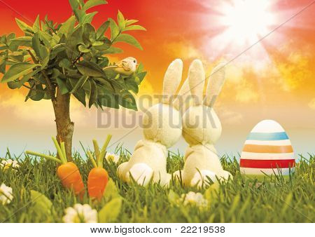 two easter-bunny sitting in a meadow beside a tree looking into the sky