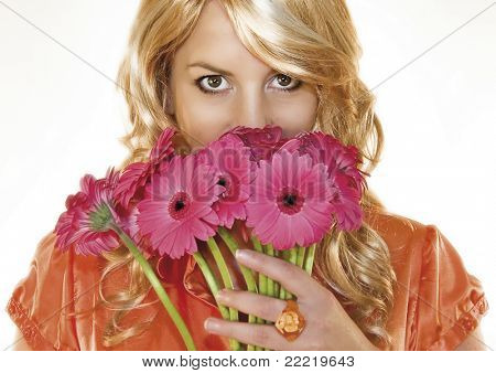 young blond woman with orange blouse holding pink flowers