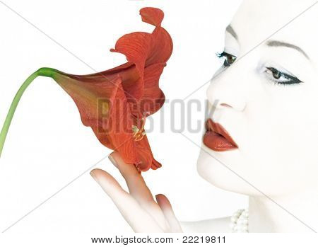 woman looking like snow-white touching a red amaryllis