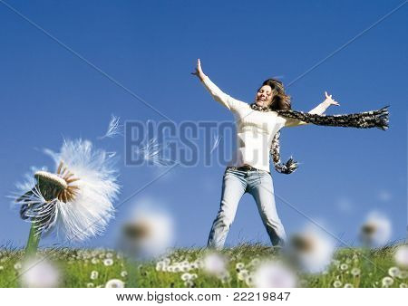 girl standing in a meadow with dandelions, wind is blowing