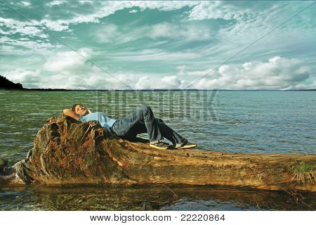 A woman lies on  a trunk in the water on a lake. The unique keyword for this collection is: lake77
