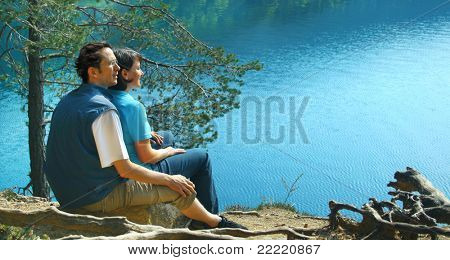 a young couple is sitting on the bank of the lake. The unique keyword for this collection is: lake77