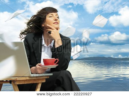 businesslady with laptop is working beside a lake. Paper is flying around. Unique keyword for this collection is: business77