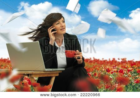 businesslady with laptop is working in a field full of poppies. Paper is flying around. Unique keyword for this collection is: business77