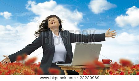 businesslady with laptop is working in a field full of poppies. Unique keyword for this collection is: business77