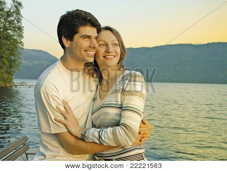 young couple is enjoying the sunset beside a lake.