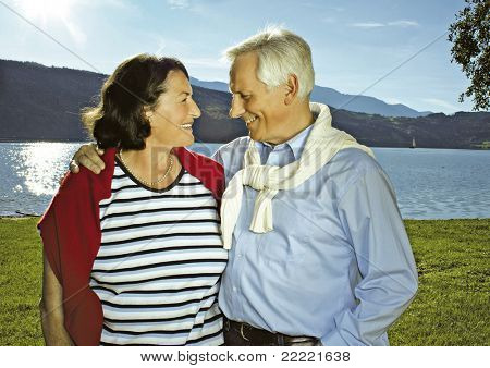 "attractive married mature couple in the sunset beside a lake. keyword for this collection is ""seniors77"""