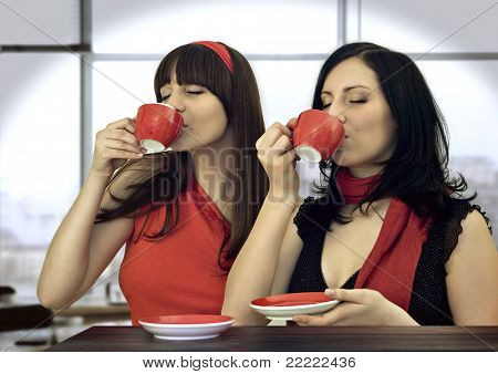 two girls drinking coffee in a cafeteria