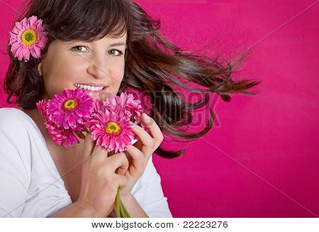 spring concept - playful girls with flowers and pink wall