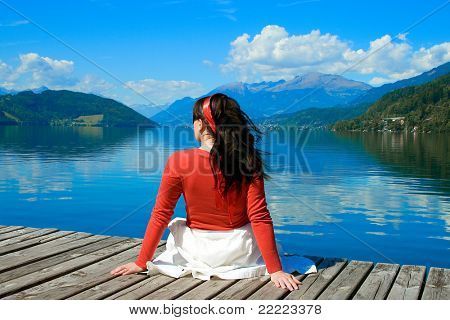 girl sitting in front of a lake