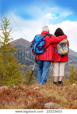 cute seniorcouple hiking in an autumn mountainlandscape. upright format.