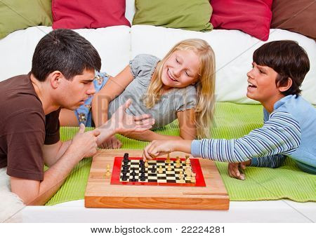 a young father is playing chess with his children
