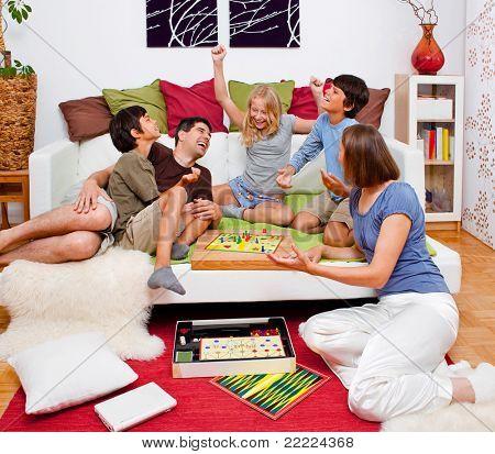 uma jovem família está jogando jogos de tabuleiro na sua cama