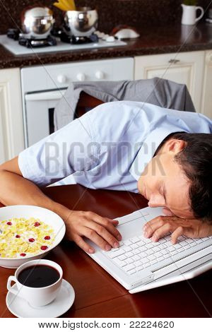 Portrait of man sleeping on laptop keypad with bowl of snacks and cup of coffee near by in the kitchen