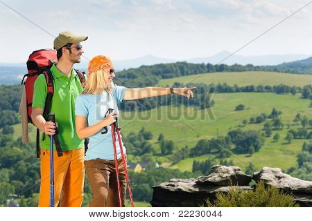 Hiking Young Couple Point At Panoramic View