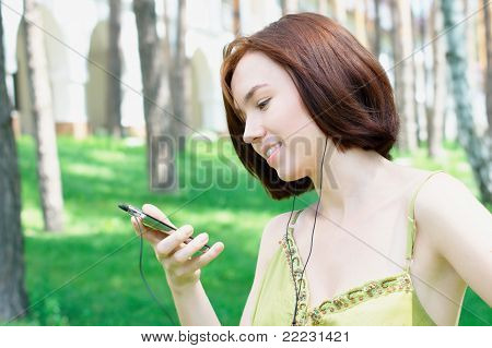 Girl listening to music at the park