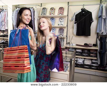 Duas mulheres elegantes com Paperbags se encontram em shopping