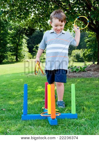 Young boy or kid playing ring toss outdoors at park during summer.