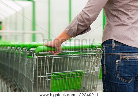 Woman - only hands to be seen - in a supermarket gets a shopping cart for the groceries