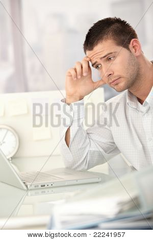 Tired businessman working on laptop in bright office.?