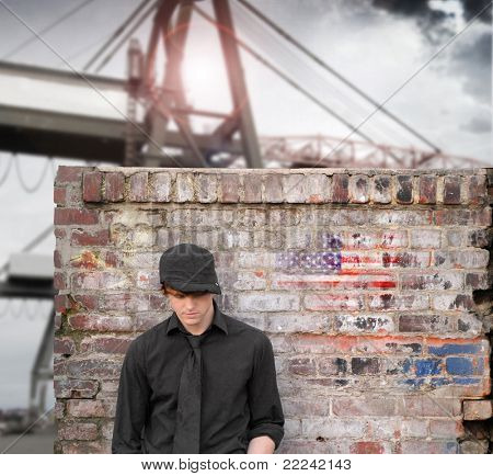 Portrait of young man in black hat against old brick wall with port in background