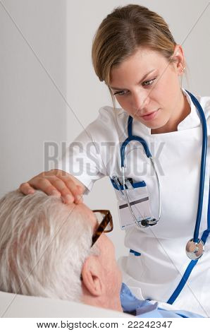 Smiling young nurse take care of old patient and checking for flu at hospital
