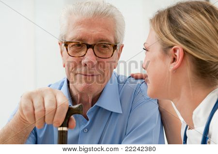 Female nurse talking and taking care of senior old man at hospital