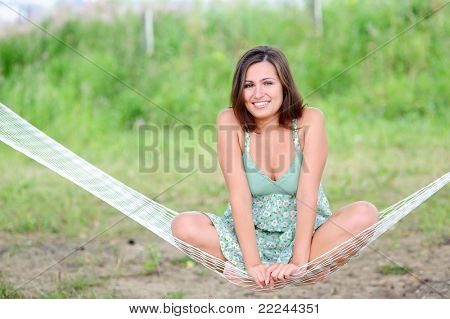 happy smiling woman sit on hammock in the park