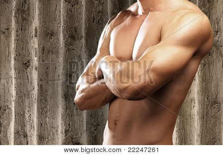 strong torso of young man against a wooden background