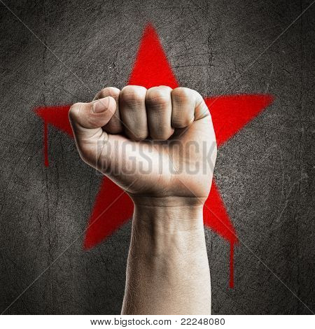 Fist against a red graffiti star on a grunge concrete wall, representing revolution and communism