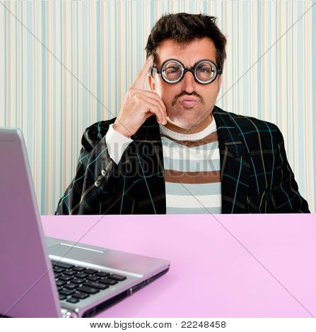 Nerd pensive man with myopic glasses and silly expression searching a solution in laptop computer
