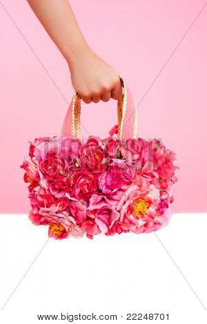 red flowers fashion bag in woman hand over pink