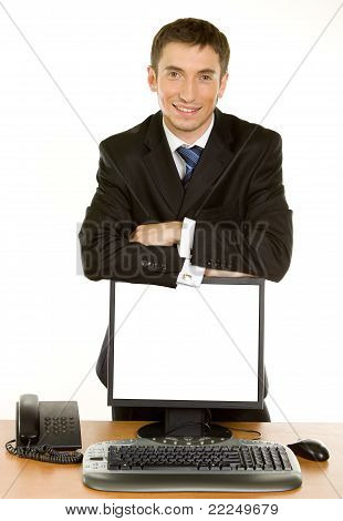 Young Businessman Leaning On A Computer Monitor