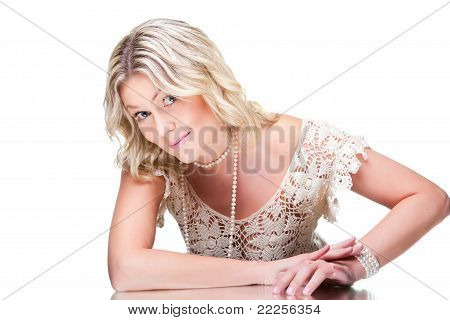 Coquettish blonde woman wearing white knitted lacy dress