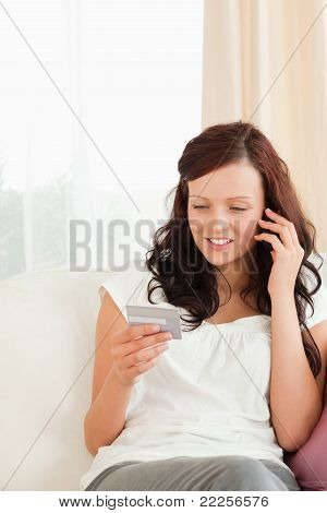 Young Woman Looking At Her Credit Card Holding Phone